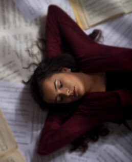 Young model laying on music sheet